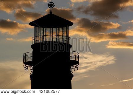 Silhouette Of Old Lighthouse Tower On A Stunning Sunset Almost Nightfall To Look For Seafood And Nav