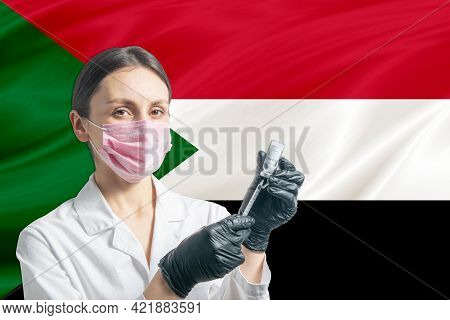 Girl Doctor Prepares Vaccination Against The Background Of The Sudan Flag. Vaccination Concept Sudan