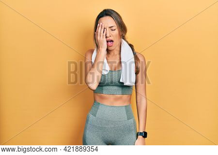 Beautiful hispanic woman wearing sportswear and towel yawning tired covering half face, eye and mouth with hand. face hurts in pain.