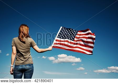 American Flag Outdoors. Woman Holds Usa National Flag Against Blue Cloudy Sky. 4th July Independence