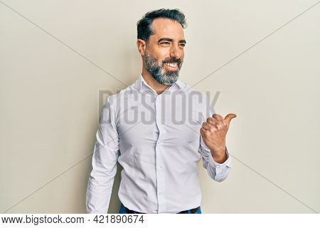 Middle age man with beard and grey hair wearing casual white shirt pointing thumb up to the side smiling happy with open mouth