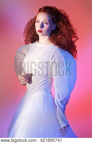 Fashion art. Portrait of a sophisticated female model with lush red curly hair posing in a white art dress. Studio portrait in mixed red color light.