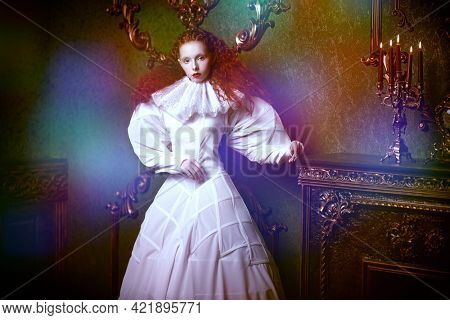 A sophisticated fashion model girl with lush red hair with fine curls poses in a vintage interior in stylized white dress with a ruffled renaissance collar. History of fashion and hairstyles.