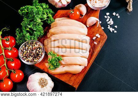 Chicken Fillet With Spices On Dark Wooden Kitchen Table. Top View With Copy Space.