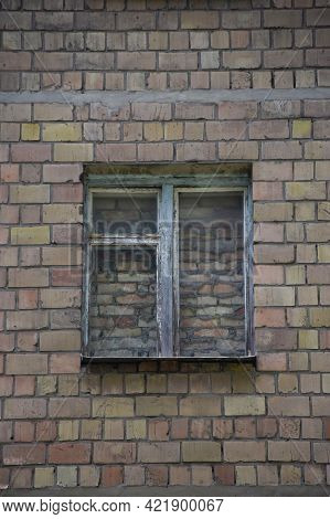 In The Center Of The Brick Wall There Is An Old Window Completely Covered With Brickwork, Walled Up