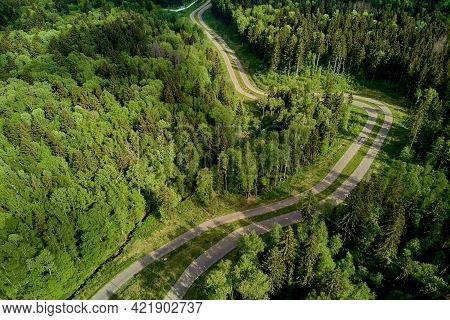 Aerial View Of A Roller Ski Trail Winding Through A Forest Landscape, An Asphalt Road In A Beautiful