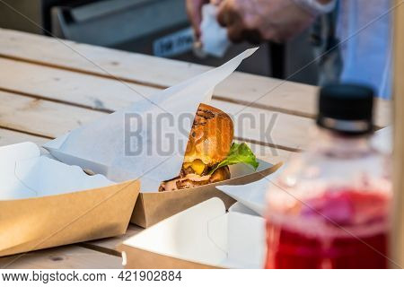 Juicy Cheeseburger With Beef Patties In A Takeaway Package On The Counter Of A Street Trade. Barbecu