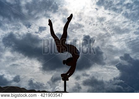 Flexible Female Circus Artist Doing Handstand Against Amazing Cloudscape. Willpower, Potential And D