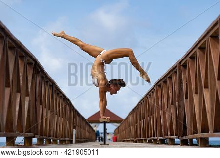 Flexible Female Circus Doing Handstand Upside Down On The Pier With Sky Background. Individuality, O