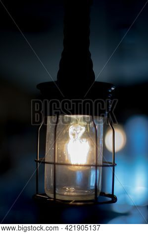 Stylish Retro Electric Light In Protective Metal Grid On Blurred Blue Background. Lamp In Metal Grid