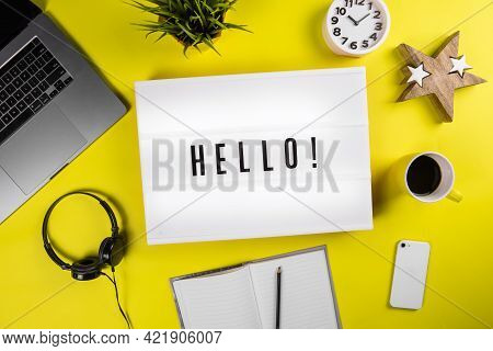 Lightbox With Message Hello On Yellow Background With Laptop, Smartphone, Headphones And Notes. Conc