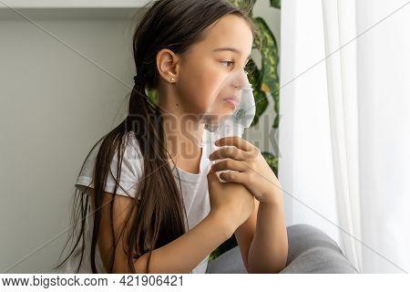 Little Girl Making Inhalation With Nebulizer At Home. Child Asthma Inhaler Inhalation Nebulizer Stea