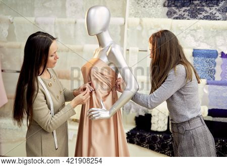 Professional Brunette Team Of Tailors, Dressmakers Or Designers Working With New Model Applying Line