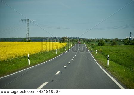 Germany - August 2015: Road Along Yellow And Green Agricultural Fields. The Autobahn Markings. High