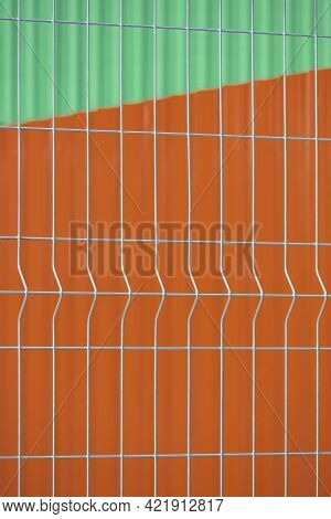 Prefabricated Grating Wire Fence Panel With Blurred Background Of Orange Steel Wall And Green Metal