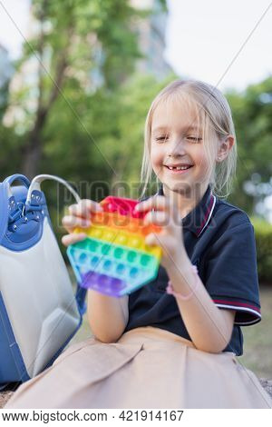 Little Caucasian Girl Is Playing With New Trendy Pop It Toy. Development Of Fine Motor Skills, Push