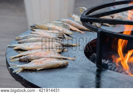 Process Of Cooking European Smelt Fish With Red Paprika Powder On Black Brazier At Summer Outdoor Fo