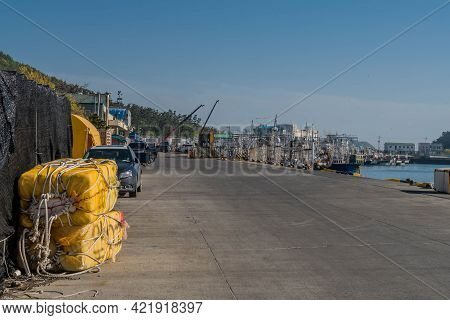 Sinjindo, South Korea; May 5, 2021: Concrete Road At Seaport Harbor With Fishing Trawlers Moored To