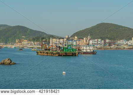 Sinjindo, South Korea; May 5, 2021: Barge With Industrial Crane On Water In Small Seaport.