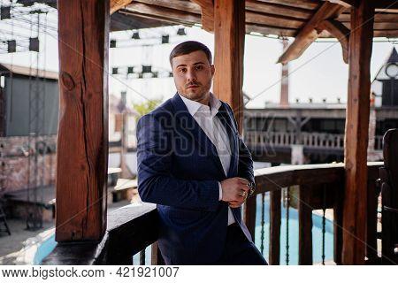 Portrait Of A Man In A Blue Jacket In A Wooden Gazebo