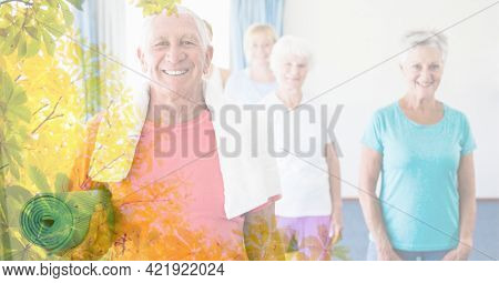Composition of smiling senior man and women exercising in fitness class with tree overlay. retirement, fitness and active lifestyle concept digitally generated image.