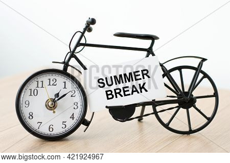 Text Summer Break On A White Card That Lies On The Clock In The Shape Of A Bicycle On The Table