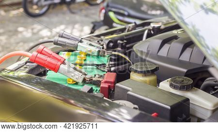 Close Up Charging Car Battery With Electricity Through Jumper Cables.