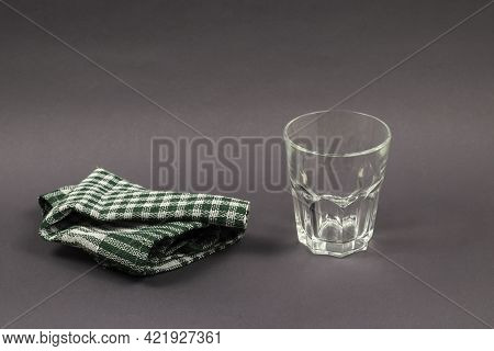 Glass And Napkin On Gray Background. Empty Glass Glass And Checkered Green Cloth Napkin. Side View.
