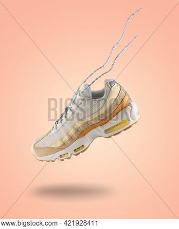 Woman Sneaker On Peach Color Background, Woman Fashion, Sport Shoe Concept, Floating Idea, Product P