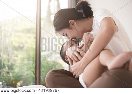 Asian Mother Love Her Son And Holding In The Embrace. Asian Mom Stay At Home With Her Son Together.