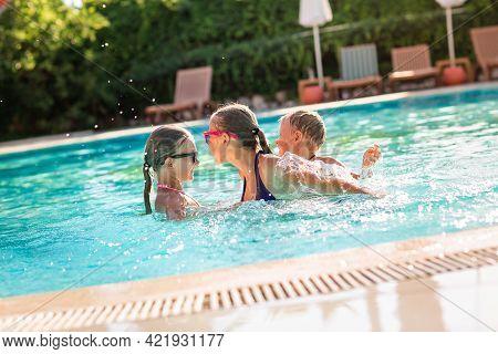 Happy Kids Having Fun At The Pool At The Resort