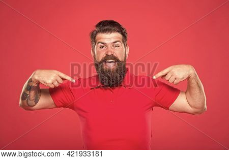 Must-have. Happy Hipster Pointing At Tshirt Red Background. Pointing Index Fingers. Pointing For Adv