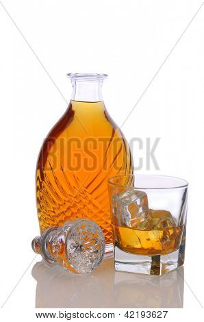 Fancy decanter and a glass of scotch on white with reflection.