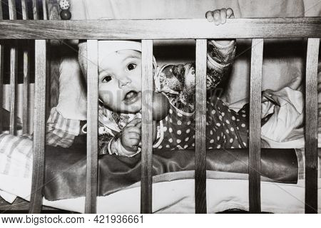 Little Baby In Bed Looking Through The Wooden Rods. Vintage Black And White Paper Photo. Early 1980s