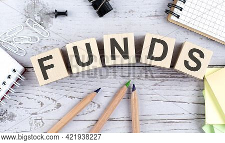 Funds Text On Wooden Block With Office Tools On Wooden Background