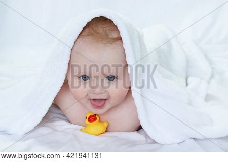 A Smiling Toddler, Covered With A Towel, Dries Off After Bathing And Plays With A Multi-colored Toy