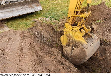 A Bucket Of Excavator With A Pile Of Earth Digs A Hole On The Construction Site. Industrial Work.