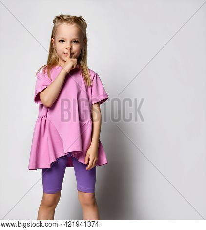 Small Blonde In Summer Clothes - Legends And A Wide T-shirt, Pressed Her Finger To Her Mouth, Hiding