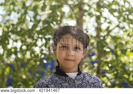 Girl 8 Year Old Against Green Tree. Day, Horizontal Shot Front View.