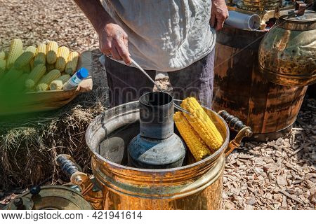 Hands Of A Cook Preparing Corn For Consumption. Corn Cobs Are Cooked Outside. The Corn Is Ready For