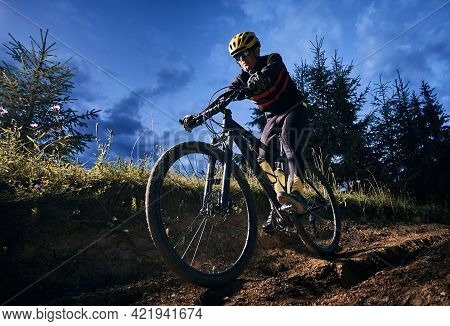 Wide Angle View Of Young Man Riding Bicycle Downhill With Blue Evening Sky On Background. Bicyclist
