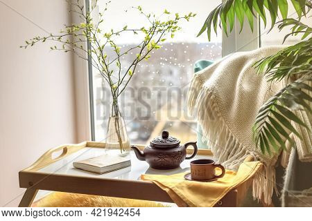 Twigs In The Bottle On The Coffee Table With A Plaid, Book, Teapot And A Cup With A Rainy City Outsi