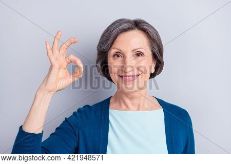 Photo Of Pretty Adorable Age Woman Wear Blue Cardigan Smiling Showing Okey Sign Isolated Green Color