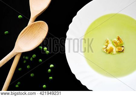 Vegetable Pea Soup With Croutons  In A White Plate On A Black Background With A Still Life With Gree