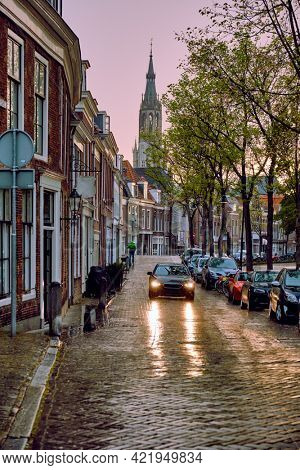 Delft cobblestone street with car in the rain with Nieuwe Kerk church tower in background. Delft, Netherlands
