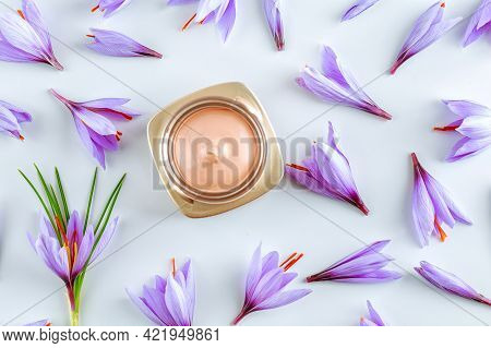 Saffron Body Cream And Many Beautiful Purple Crocus Flowers On A White Background. The Use Of Saffro