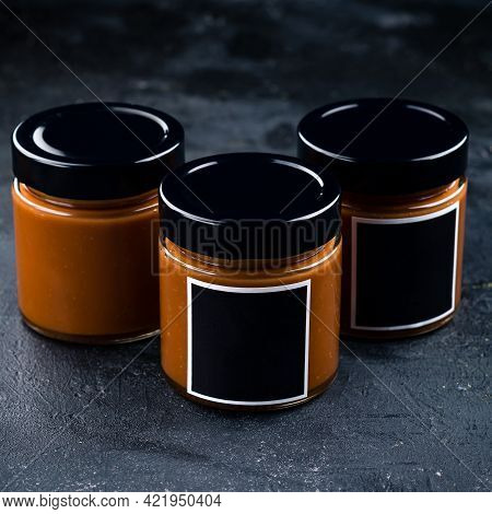 Homemade Salted Caramel Sauce In A Vintage Jar On A Dark Slate, Stone Or Concrete Background.