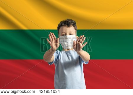 Little White Boy In A Protective Mask On The Background Of The Flag Of Lithuania. Makes A Stop Sign