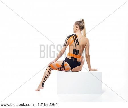 Physio tapes applied to the body of a young athletic woman isolated on white background. Physiotherapy, kinesio taping, kinesiology and recovery treatment.