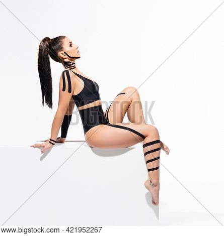 Physio tapes applied to the body of a young athletic woman isolated on white. Physiotherapy, kinesio taping, kinesiology and recovery treatment concepts.